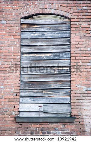 Boarded up window of antique building - stock photo