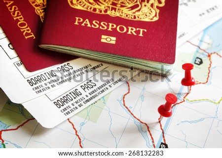 Boarding pass and passport on map with thumbtack concept for travel and vacations - stock photo
