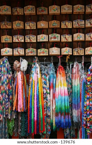 Boards with wishes on them, hung at a shrine. Origami cranes, made to pray for good health. - stock photo