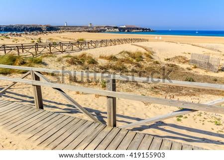 Boardwalk and fence on sandy beach, Tarifa, Spain - stock photo