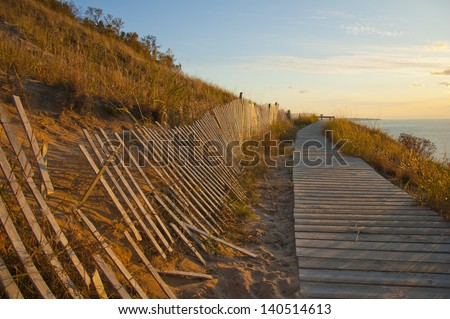 Boardwalk and fence on sandy cliff overlook at sunset - stock photo