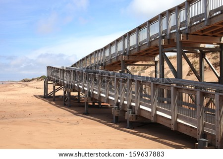 Boardwalk leading to a sandy beach - stock photo