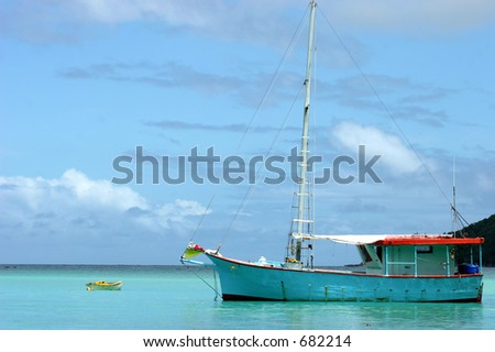 Boat anchored in a peaceful bay - stock photo