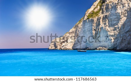 Boat anchored on Navagio beach (also known as shipwreck beach), Zakynthos island, Greece.Side view of Navagio beach in Greece with cruiser anchoring next to beach - stock photo