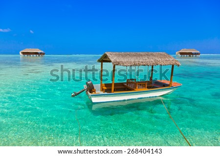 Boat and bungalow on Maldives island - nature travel background - stock photo