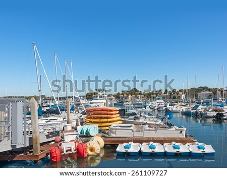 Boat and kayak rentals in busy marina. Reflections of boats and other pleasure craft in the calm water. Blue sky with room for text.  - stock photo