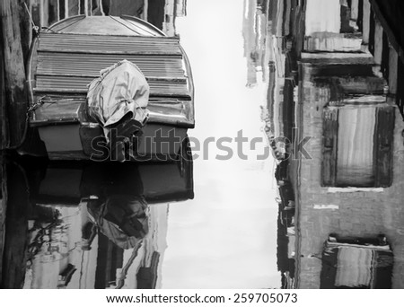 Boat and reflection of houses in the water. Narrow canal in Venice. Aged photo. Black and white. - stock photo