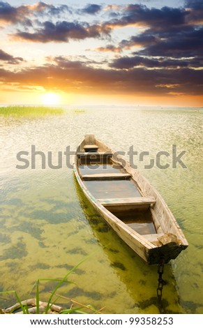 Boat at coast against a sunset. Nature composition. - stock photo