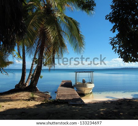 Boat at dock under coconut tree on tropical shore with calm water of the Caribbean sea, Bocas del Toro, Panama - stock photo