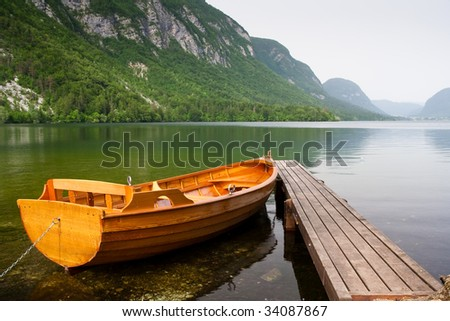 boat berth on the shore of bohinj lake in Slovenia with mountain as background. This photo truly expresses the tranquility and unsploit nature of the eastern europe country. - stock photo