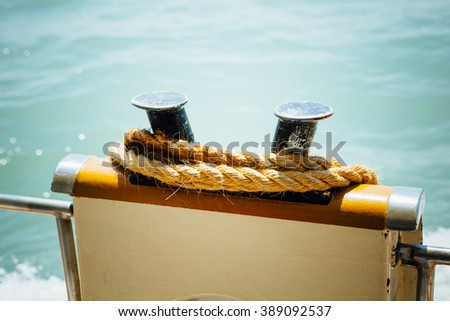 boat bollard (bitt) with rope against water background - stock photo