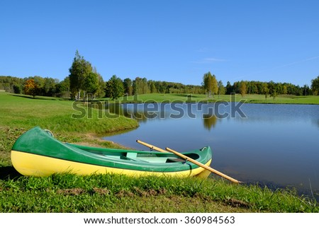 boat by the lake in countryside landscape in summer - stock photo
