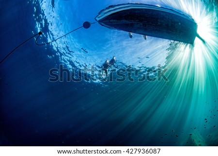 boat chain anchor from underwater with sun rays - stock photo