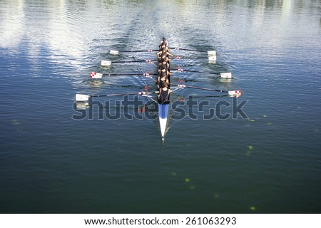Boat coxed eight Rowers rowing on the tranquil lake - stock photo