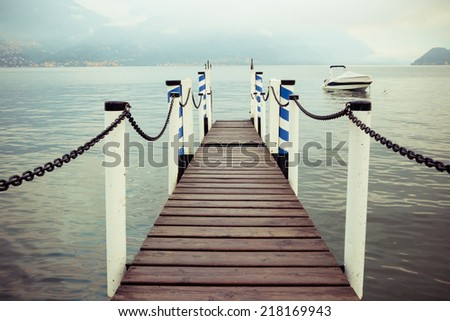 Boat dock in Menaggio, Lake Como Italy. Nautical, travel, European vacation, boating and yachting concept. High contrast. Vintage processed  - stock photo