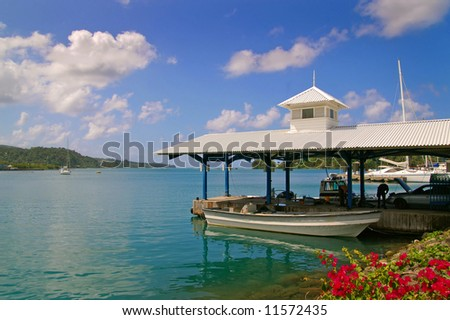 boat docked at a tropical harbor on a sunny day - stock photo