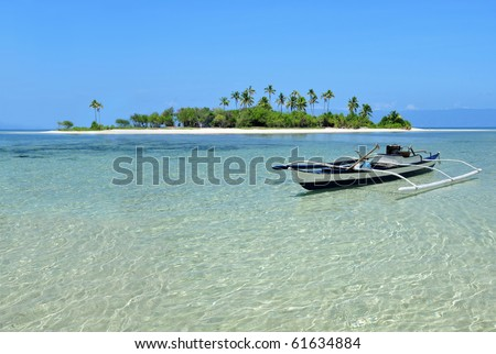 Boat docked on a beautiful pristine tropical island beach. - stock photo