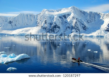 boat dwarfed by antarctic mountains - stock photo