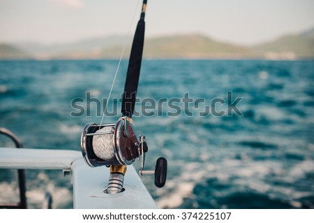 Boat fishing rods over a beautiful cloudy seascape horizontal - stock photo