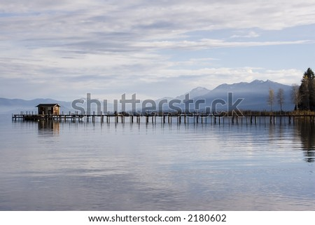 Boat house and pier on lake tahoe,with clouds and mountains. - stock photo