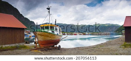 Boat houses, and fishing boats reflected in mountain fjords. - stock photo