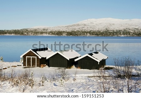 Boat houses by a lake in winter - stock photo