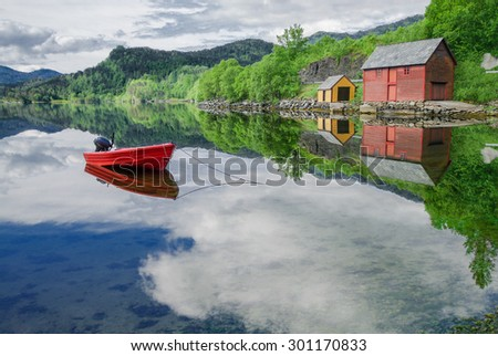 Boat in a Quiet Cove:  A small boat sits at anchor along the shore of a fjord in southwest Norway.  - stock photo
