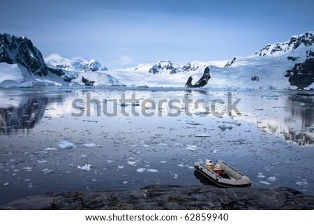 boat in Antarctic waters, mountains on the background - stock photo