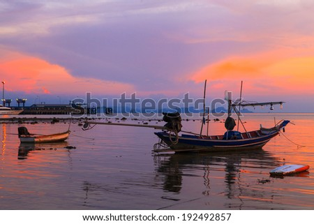 Boat in sea at sunset - stock photo