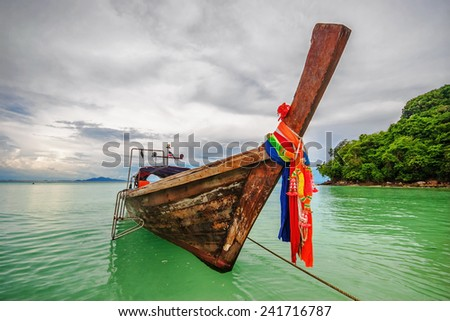 Boat in the tropical sea under gloomy dramatic sky. Thailand  - stock photo