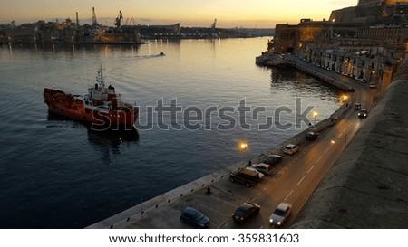 Boat in Valletta harbor at dusk, Malta, Europe - stock photo
