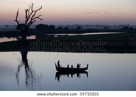 boat is floating near lonely tree in calm water - stock photo