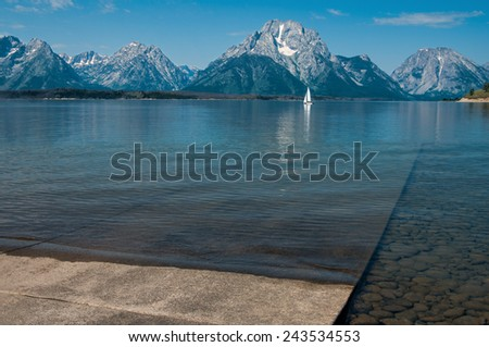 Boat Launch Ramp:  Shallow waves reach a concrete ramp that slopes gradually into Jackson Lake in Grand Teton National Park.  - stock photo
