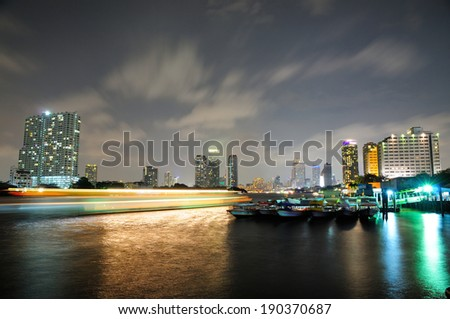 Boat Light Trails Along Chao Phraya River in Bangkok with a View of Buildings at Night  - stock photo