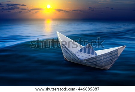 Boat made from business paper graph on sea with sun light and sky.For business financial ideas concept. - stock photo