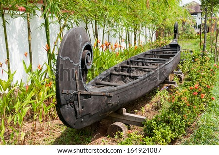 boat made of wood Kerala India. Old fisherman boat. snake boat India. Canoes kept in a garden as a vintage show piece - stock photo