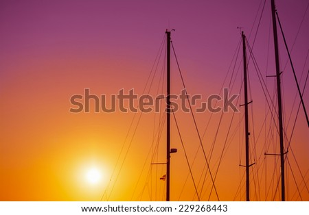 boat masts silhouette under a colorful sunset. Shot in Alghero, Italy - stock photo