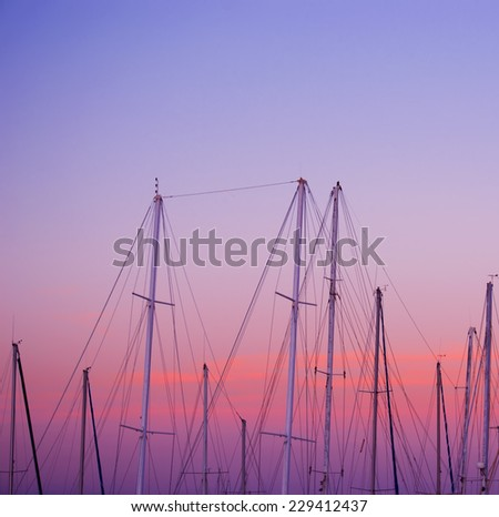 boat masts under a pink and orange sunset. Shot in Alghero, Sardinia - stock photo