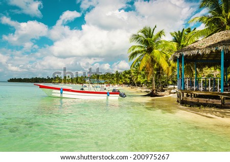 Boat moored off the coast of the island full of palm trees, Caribbean Islands  - stock photo