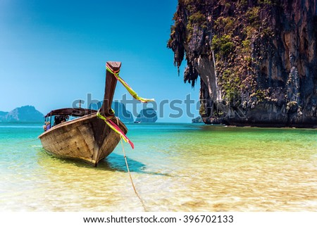 Boat next to a big rock in the sea, Thailand - stock photo