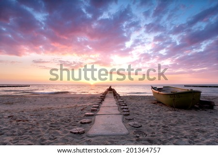 boat of a fisherman is located on the beach during sunset, burning sky in summer at Baltic sea - stock photo