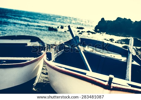 boat on a sandy shore on rocky coastline background - stock photo