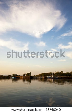 Boat on River Channel with Sun and Clouds - stock photo