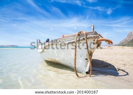 Boat on sandy beach - stock photo