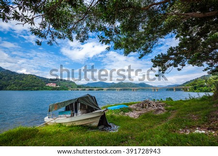 Boat on shore of a tropical lake and islands in cloudy blue sky. Belum resort, Banding, Temenggor Lake. Malaysia - stock photo