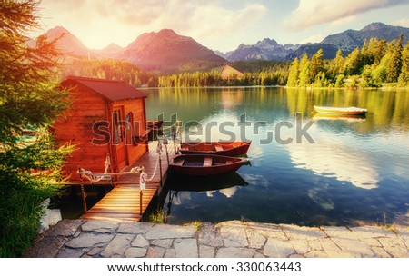 Boat on the dock surrounded by mountains at sunset. Fantastic Shtrepske Pleso High Tatras. Slovakia, Europe. - stock photo