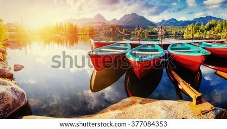 Boat on the dock surrounded mountains. Fantastic Shtrbske Pleso High Tatras. Slovakia, Europe.  - stock photo