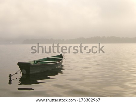Boat on the foggy lake - stock photo