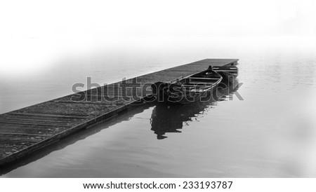 Boat on the foggy lake - stock photo