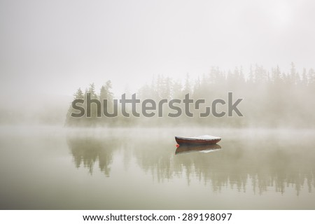 Boat on the lake at morning fog. - stock photo